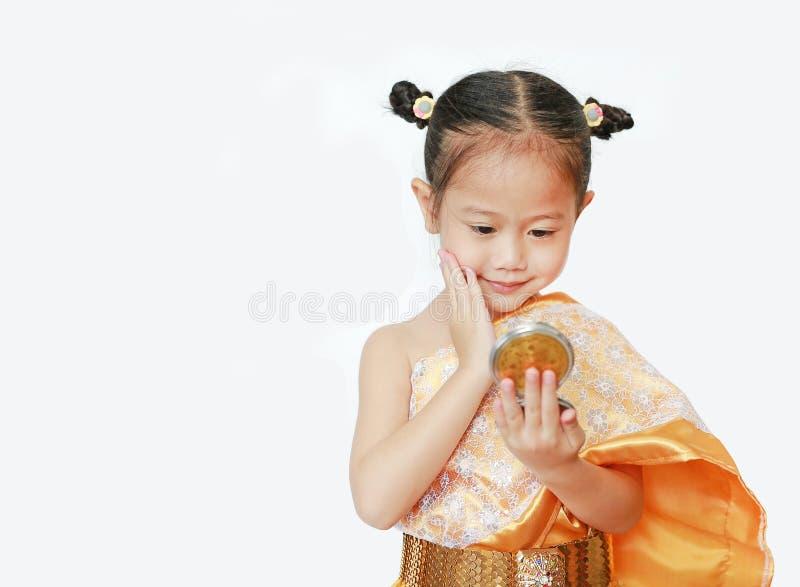 Stående av den asiatiska barnflickan i den traditionella thai klänningen som ser spegeln som isoleras på vit bakgrund arkivfoto