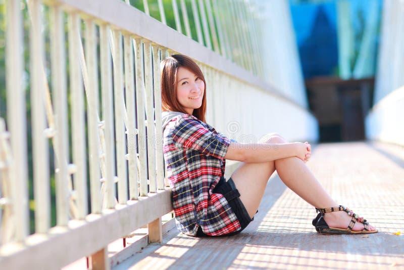Stående av den asiatiska flickan 20 gamla år posera utomhus kläderplädskjortan arkivbild