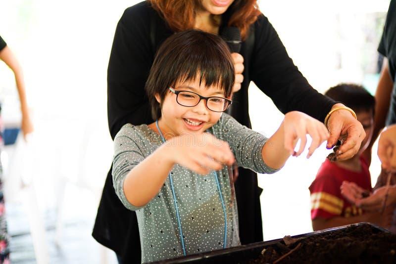 Stående av den asiatiska flickan som rymmer daggmasken vid hennes händer med f arkivfoto