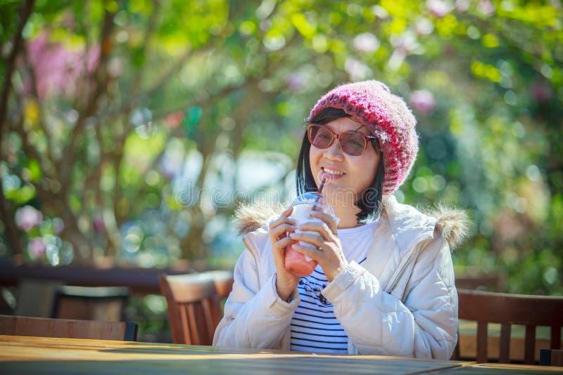Stående av den asiatiska kvinnan för 40-talår med kall saftig dricka bottl royaltyfri foto