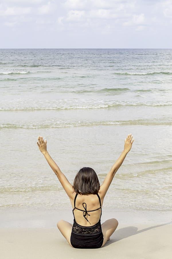Stående av den asiatiska kvinnan som bär en sittande yoga för baddräkt på den strandbakgrundshavet och himlen arkivfoto