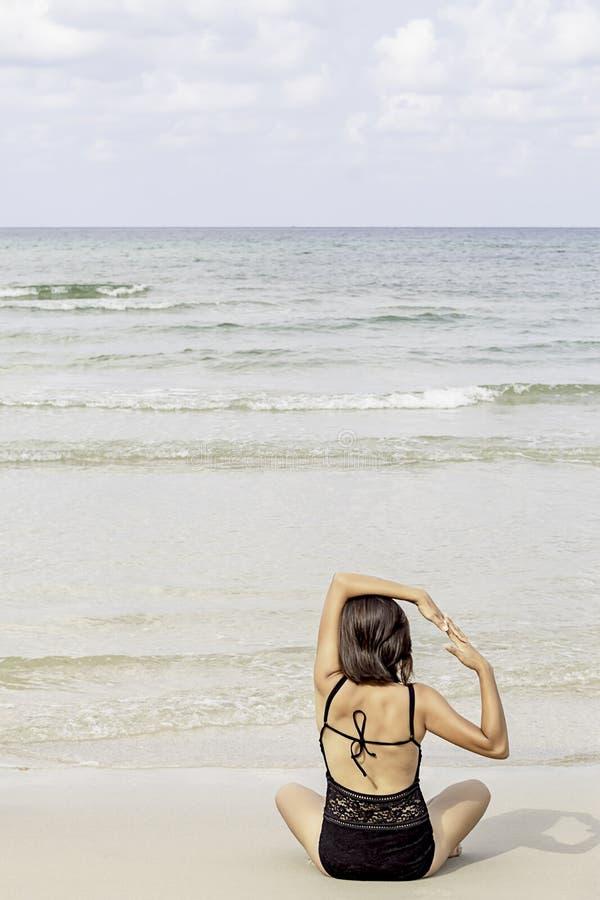 Stående av den asiatiska kvinnan som bär en sittande yoga för baddräkt på den strandbakgrundshavet och himlen royaltyfri bild