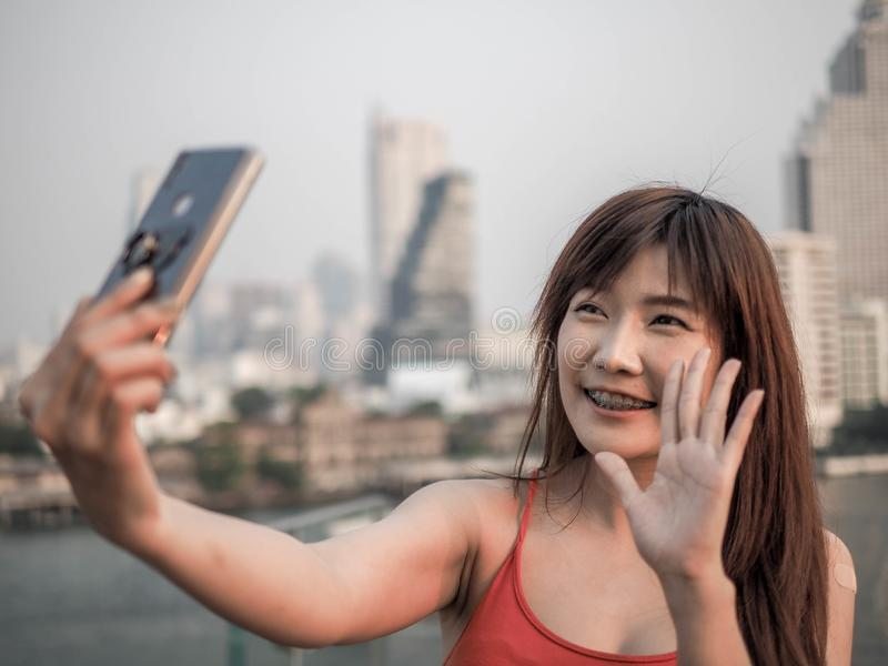 Stående av den asiatiska kvinnan som gör en video appell genom att använda den smarta telefonen arkivbilder