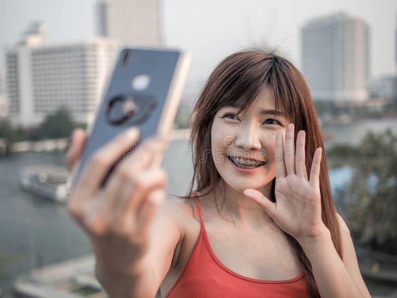 Stående av den asiatiska kvinnan som gör en video appell genom att använda den smarta telefonen fotografering för bildbyråer