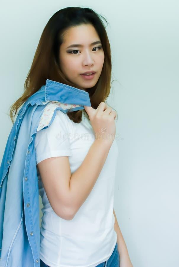 Stående av den asiatiska kvinnan som poserar med hennes jeanomslag royaltyfri bild