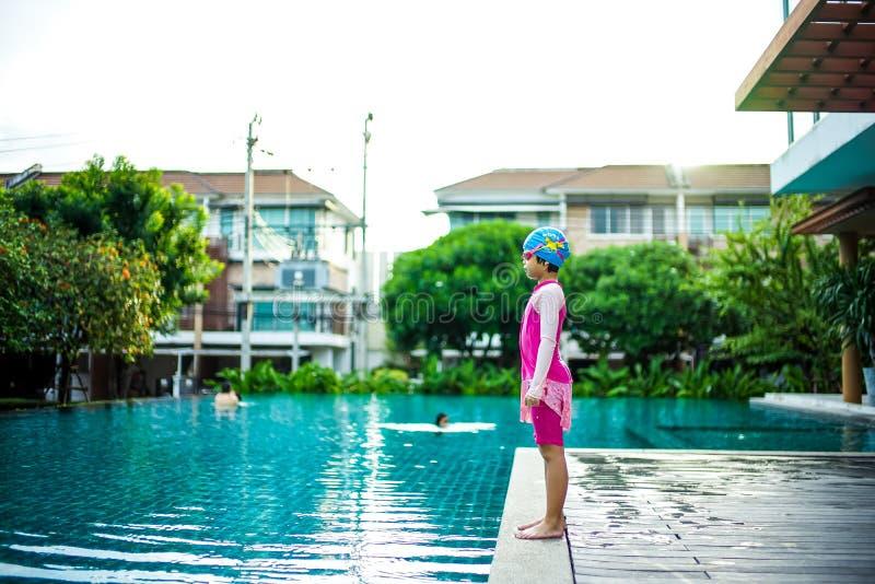 Stående av den asiatiska lilla flickan som lyckligt simmar i pölen arkivbild