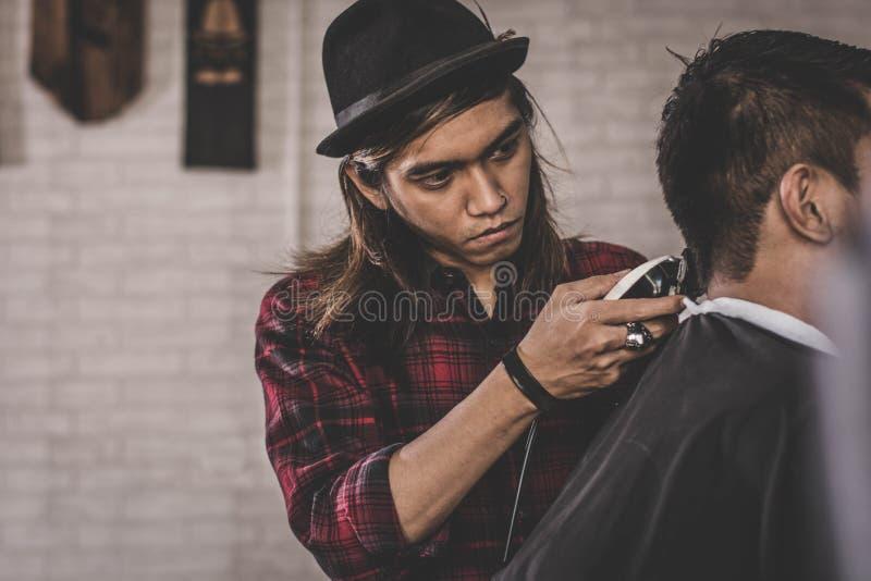 Stående av den asiatiska mannen med långt brunt hårarbete som barberare med dräkten arkivbild
