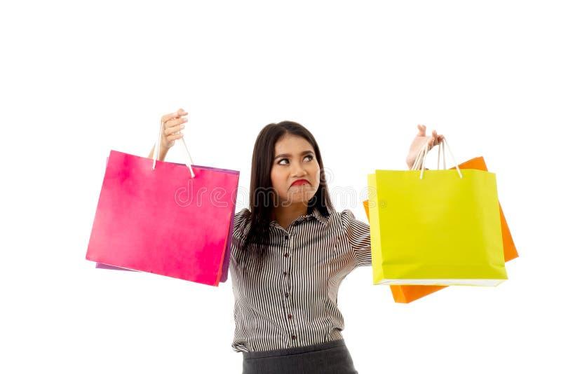 Stående av den asiatiska unga damen att rulla hennes ögon som rymmer färgrika shoppa påsar Affärskvinnan med att shoppa terapi i  arkivbilder