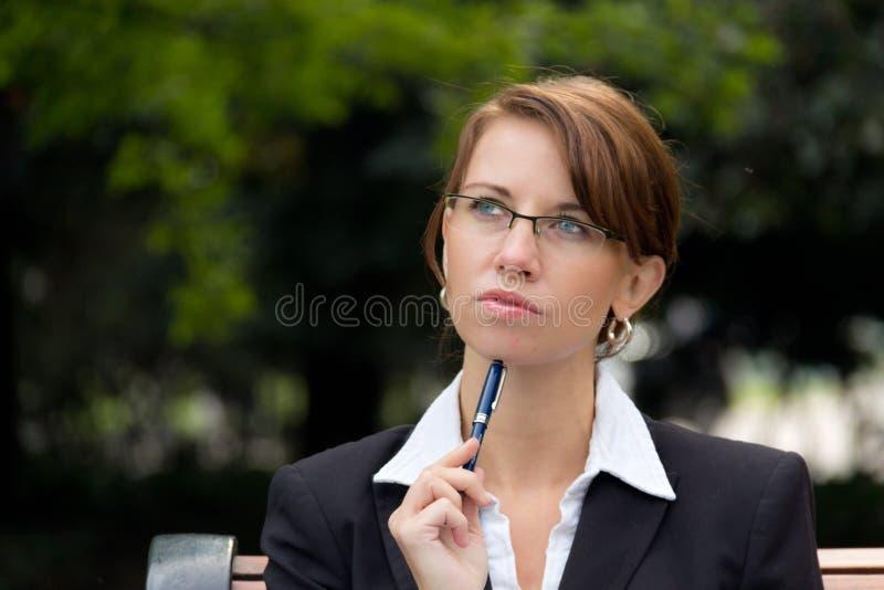Stående av den attraktiva affärskvinnan med att tänka för exponeringsglas arkivfoto