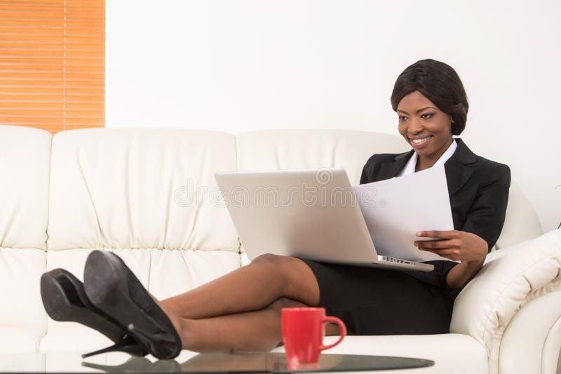 Stående av den attraktiva affärskvinnan som arbetar på bärbara datorn fotografering för bildbyråer