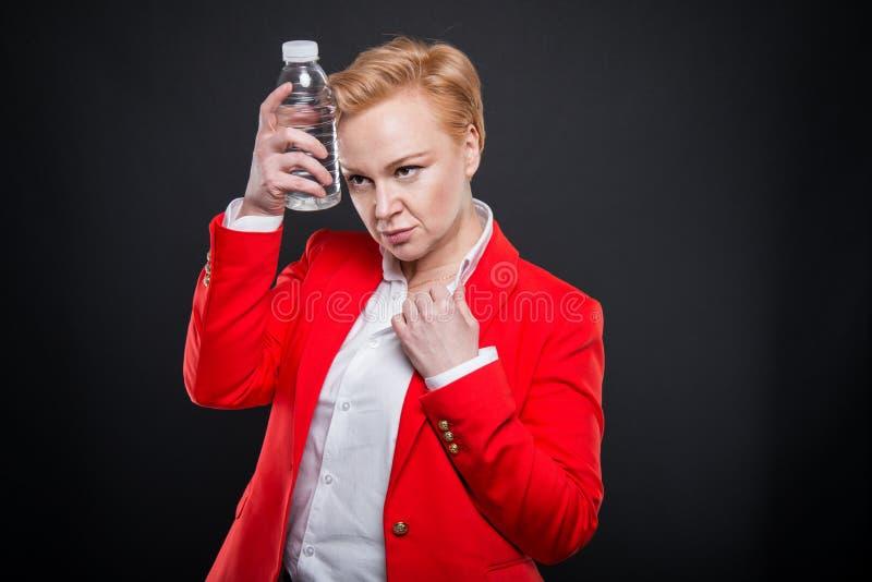 Stående av den attraktiva affärskvinnan som kyler med flaskan av wat royaltyfri fotografi