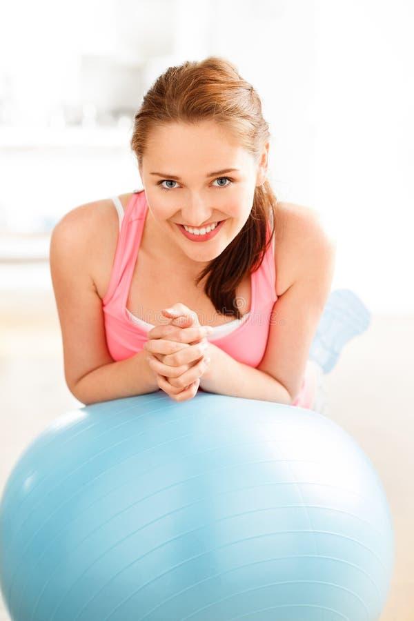 Stående av den attraktiva avslappnande konditionbollen för ung kvinna på idrottshallen royaltyfria bilder