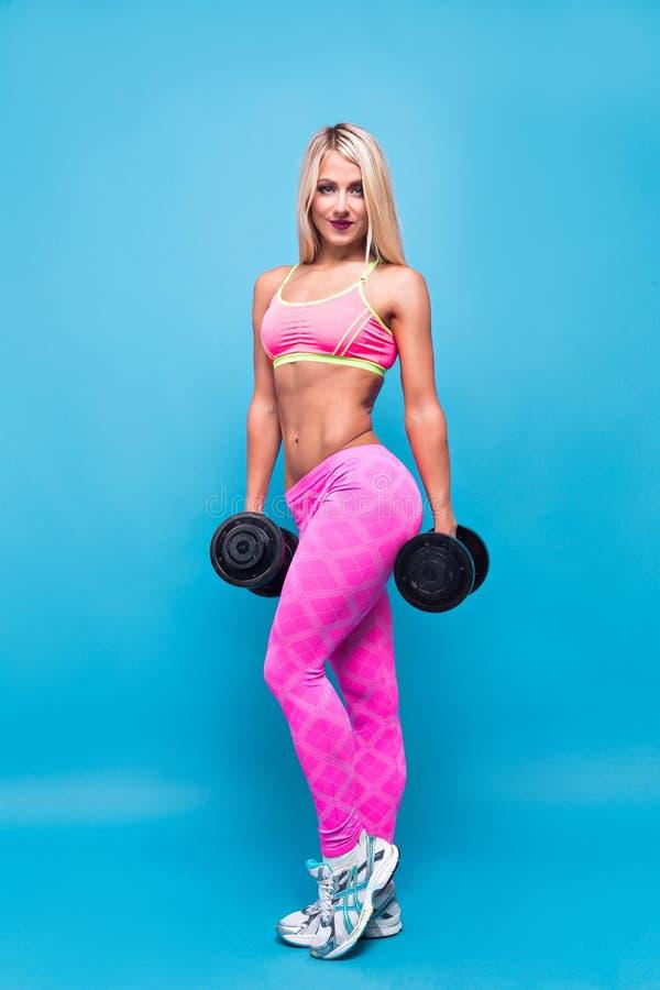 Stående av den attraktiva blonda kvinnan i den rosa sportswearen som poserar med hantlar på blå bakgrund arkivfoton