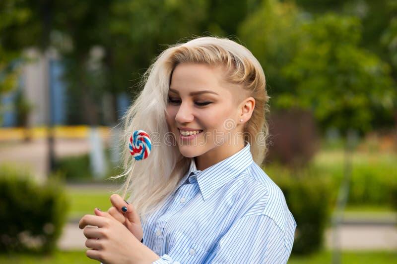 Stående av den attraktiva blonda kvinnlign med godisen fotografering för bildbyråer