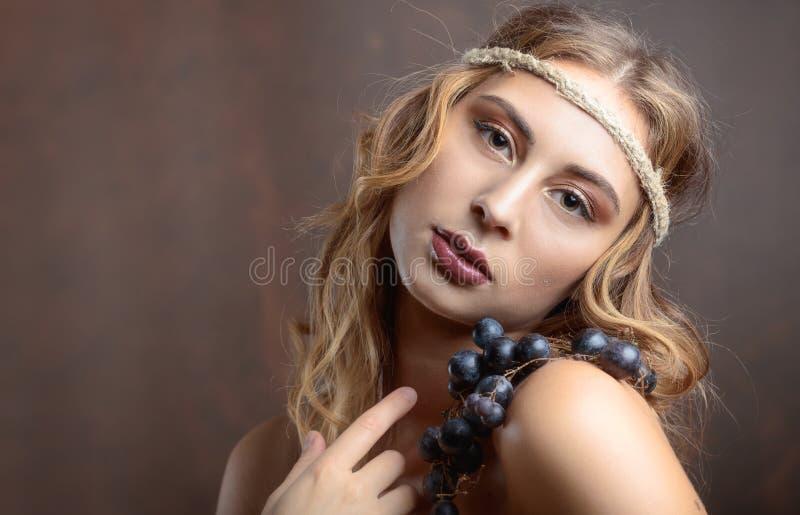 Stående av den attraktiva blondinen med blåa druvor arkivfoton