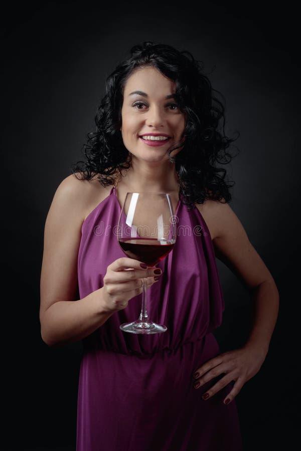 Stående av den attraktiva brunetten i lång aftonklänning med exponeringsglas av rött vin royaltyfria bilder