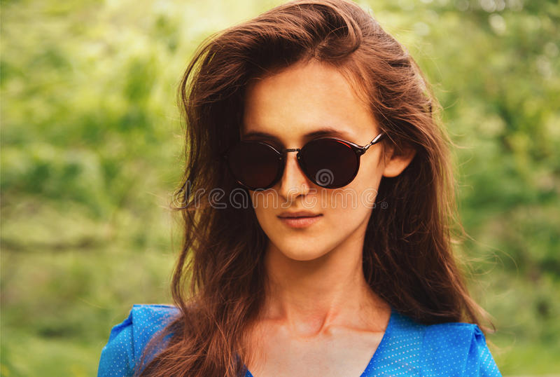 Stående av den attraktiva brunettkvinnan i solglasögon royaltyfria bilder