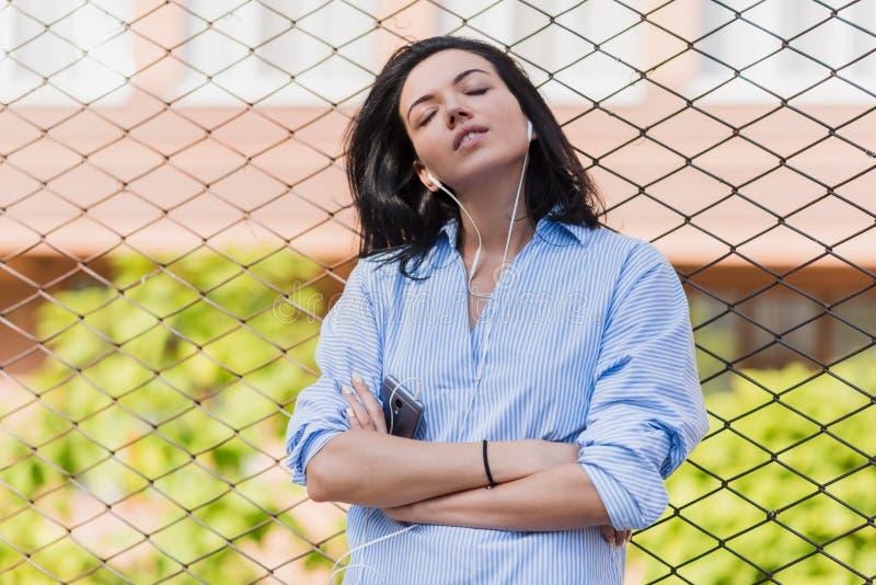 Stående av den attraktiva brunettkvinnan med att tycka om tiden, den lyssnande musiken och den väntande vännen på stadsgatan Ung  royaltyfria bilder