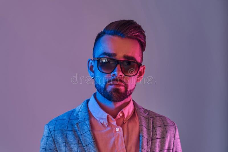 Stående av den attraktiva eftertänksamma mannen i checkeretblazer och sunglasse royaltyfria foton