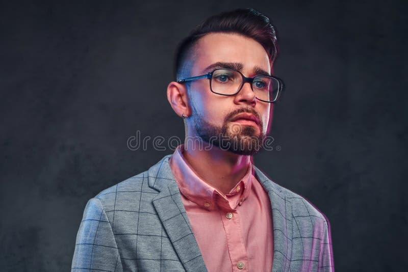 Stående av den attraktiva eftertänksamma mannen i rutig blazer, rosa skjorta och exponeringsglas arkivbilder