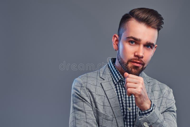 Stående av den attraktiva eftertänksamma mannen i rutig skjorta och grå blaser arkivfoto