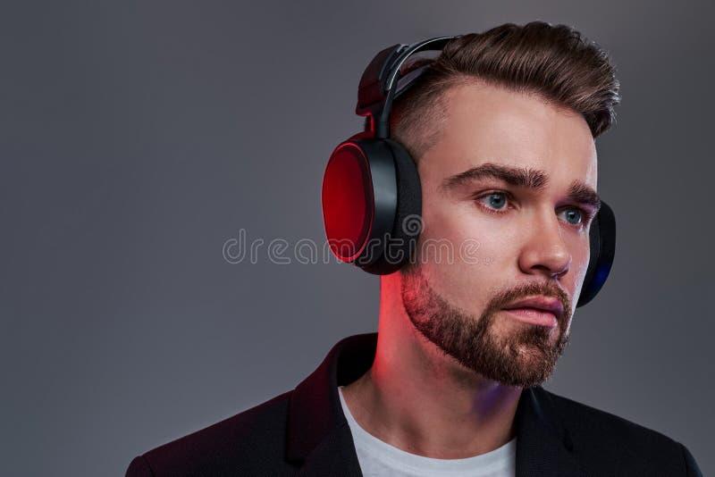 Stående av den attraktiva eftertänksamma mannen i trådlös hörlurar royaltyfri bild