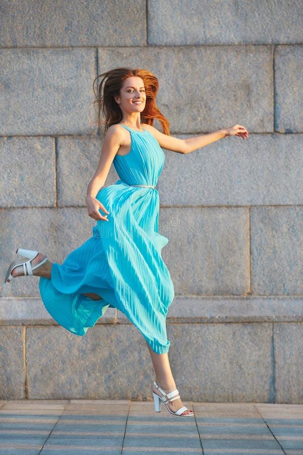 Stående av den attraktiva eleganta unga kvinnan i en blå klänning som hoppar på trottoaren royaltyfri fotografi