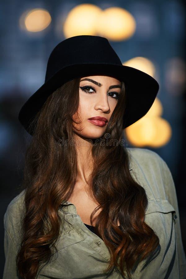 Stående av den attraktiva eleganta unga kvinnan med den svarta hatten arkivfoto