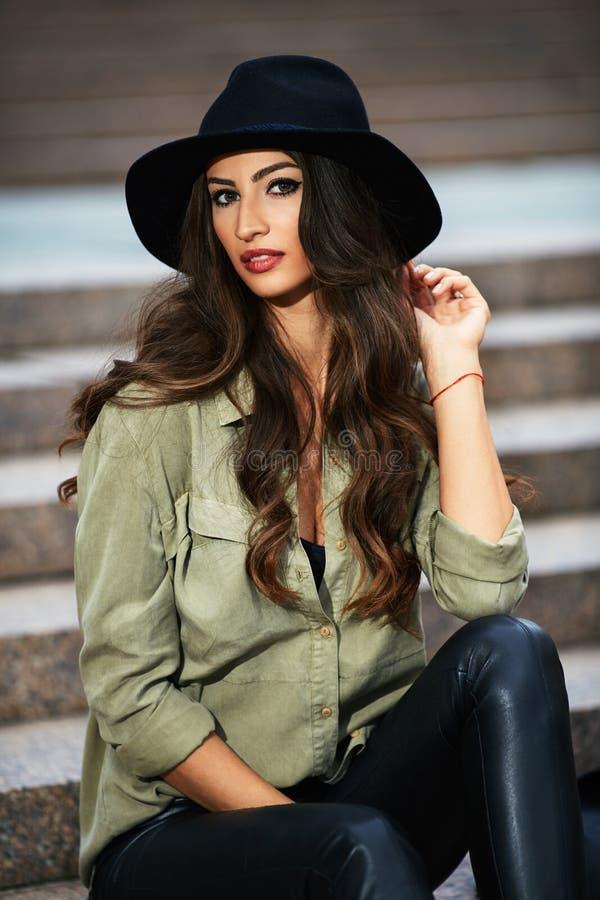 Stående av den attraktiva eleganta unga kvinnan med den svarta hatten arkivbild