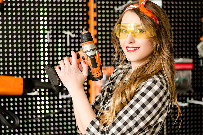 Stående av den attraktiva försäljaren med långt blont hår och gula exponeringsglas i hemförbättringlager med en drillborr fotografering för bildbyråer
