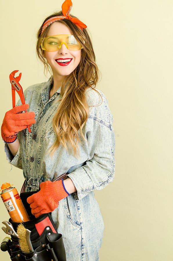 Stående av den attraktiva försäljaren med långt blont hår och gula exponeringsglas i hemförbättringlager med plattång arkivfoton