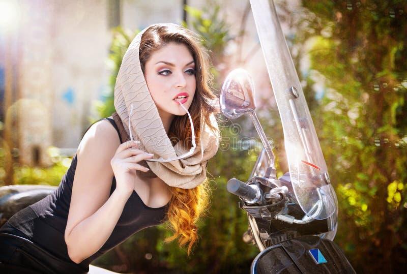 Stående av den attraktiva flickan för mode med sjaletten och solglasögon förutom en gammal sparkcykel royaltyfri foto