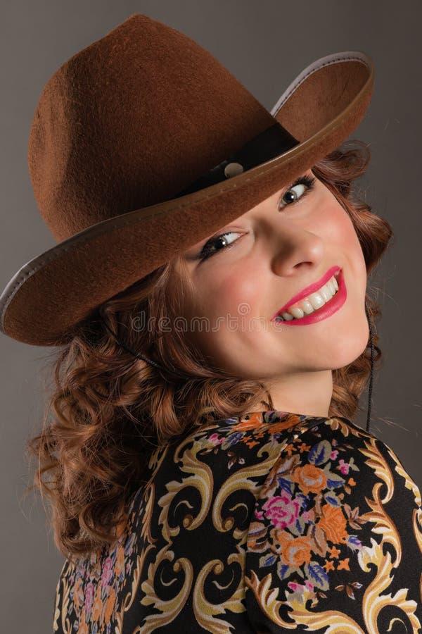 Stående av den attraktiva flickan med änglalikt leende i cowboyhatt arkivfoton