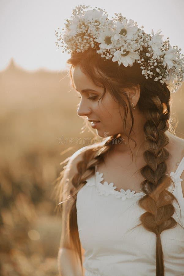 Stående av den attraktiva flickan med blommakransen och flätade trådar i den vita klänningen i sommarfält på solnedgången arkivfoto