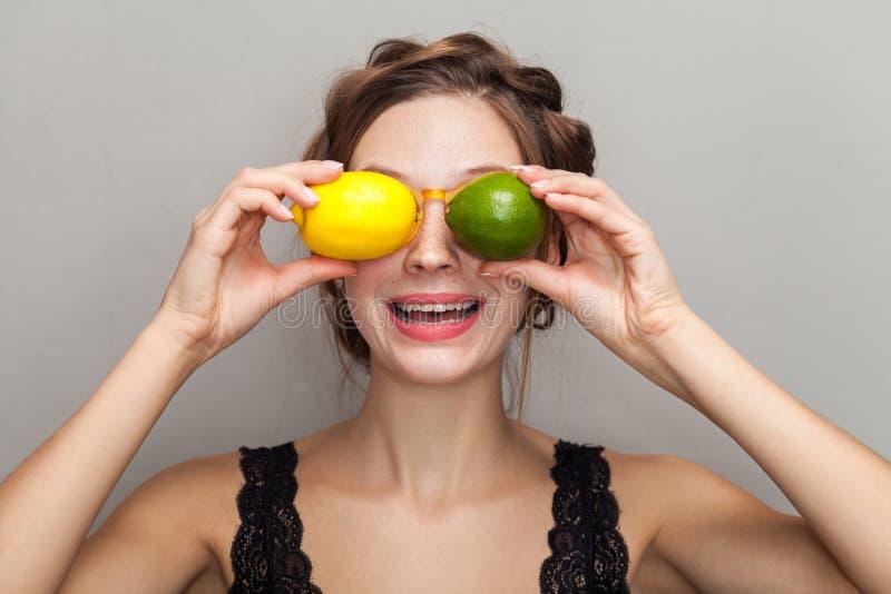 Stående av den attraktiva kvinnan i exponeringsglas som rymmer limefrukt och citron I royaltyfri fotografi