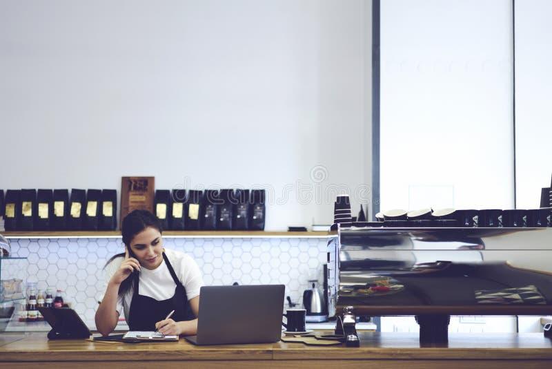 Stående av den attraktiva kvinnliga baristaen som arbetar i kafeteria royaltyfri bild