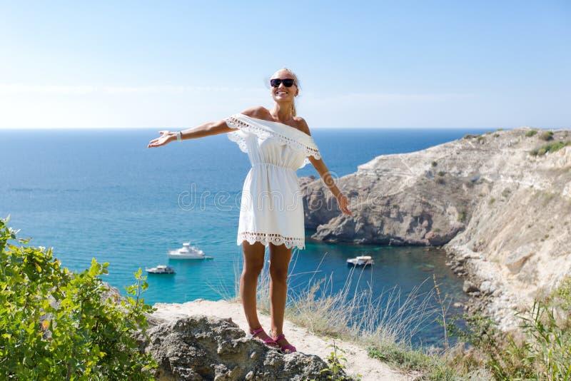 Stående av den attraktiva kvinnliga personen i vita sundress mot seascape arkivbild