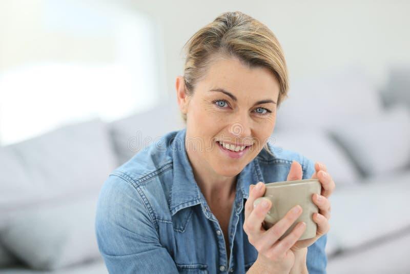 Stående av den attraktiva mogna blonda kvinnan med koppen kaffe arkivfoto