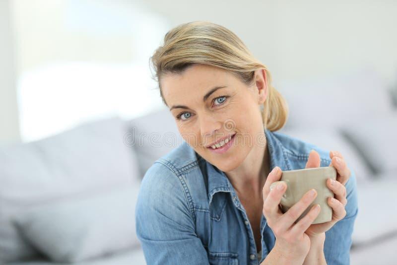 Stående av den attraktiva mogna blonda kvinnan med koppen kaffe royaltyfri bild