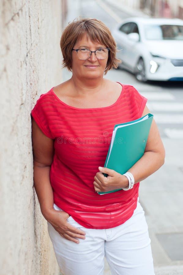 Stående av den attraktiva mogna kvinnan med en affärsmapp och ett G royaltyfria bilder