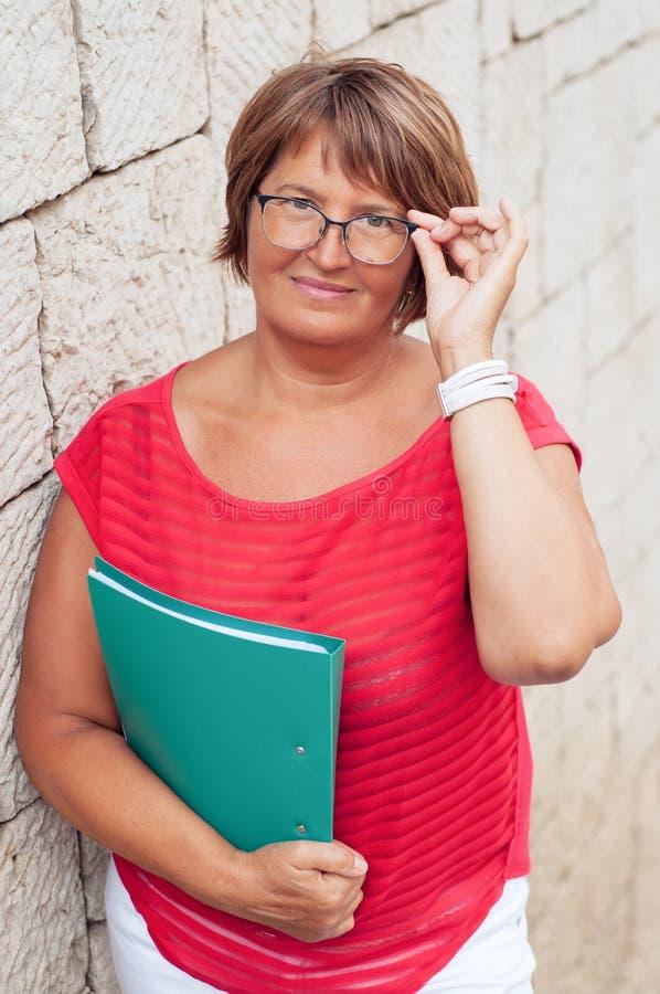 Stående av den attraktiva mogna kvinnan med en affärsmapp och exponeringsglas royaltyfri bild