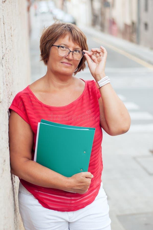 Stående av den attraktiva mogna kvinnan med en affärsmapp och exponeringsglas royaltyfria foton