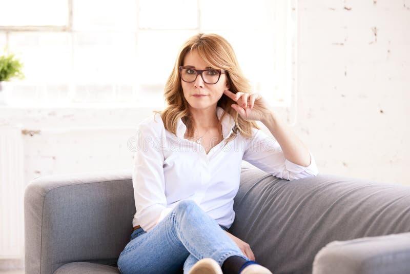 Stående av den attraktiva mogna kvinnan som kopplar av på soffan arkivfoto