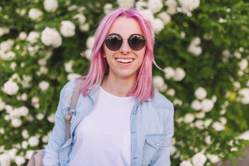 Stående av den attraktiva nätta Caucasian härliga kvinnan med rosa hår som ler mot att blomma trädet med vita blommor arkivfoto