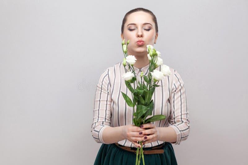 Stående av den attraktiva romantiska älskvärda unga kvinnan i randig skjorta och grön kjolinnehavbukett av vita blommor och överf arkivfoto
