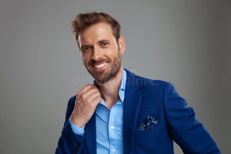 Stående av den attraktiva smarta tillfälliga mannen som rymmer den blåa skjortakragen arkivfoton