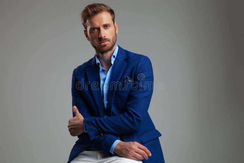Stående av den attraktiva smarta tillfälliga mannen som sitter och rymmer armbågen arkivbilder