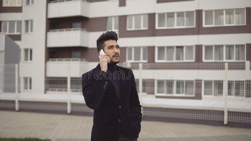 Stående av den attraktiva spensliga affärsmannen i formell dräkt som talar på smartphonen mot bakgrunden av affärsmitten royaltyfria bilder
