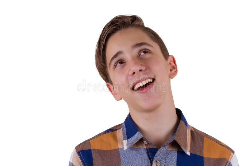 Stående av den attraktiva tonåriga pojken som ler och ser fotograferas upp i en studio bakgrund isolerad white arkivfoto