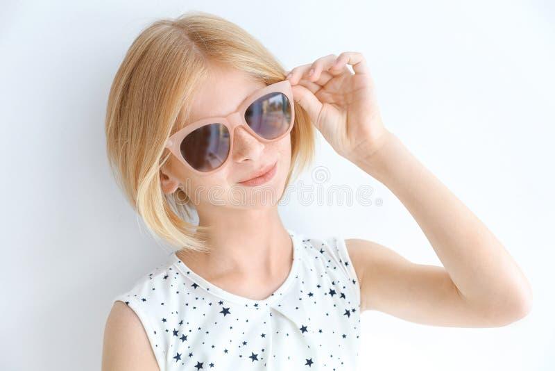 Stående av den attraktiva tonåringflickan i solglasögon som isoleras på vit arkivfoto